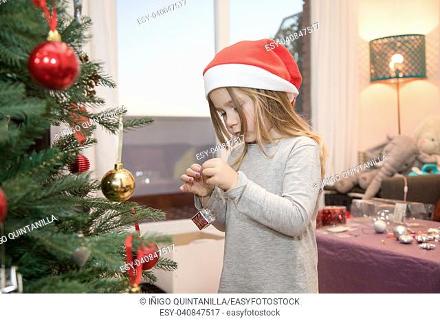 four years blonde cute girl with red Santa Claus hat, decorating Christmas tree at home