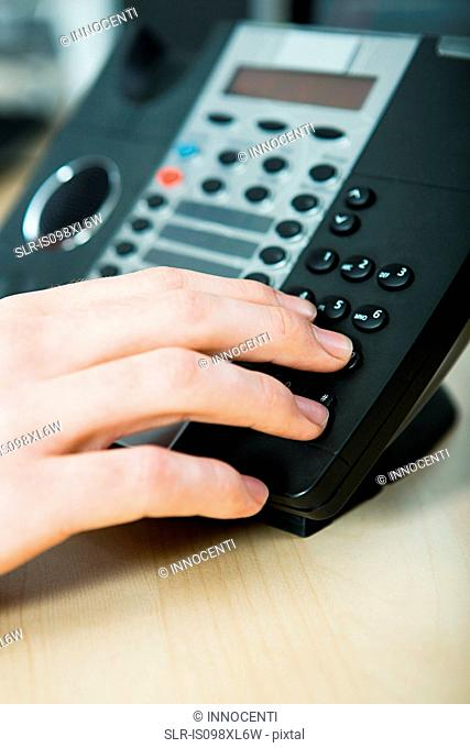 Office worker dialling telephone