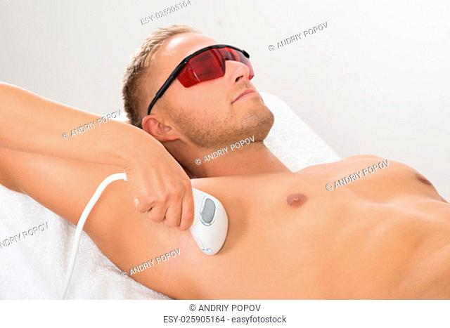 Beautician Giving Laser Epilation Treatment On Man's Armpit