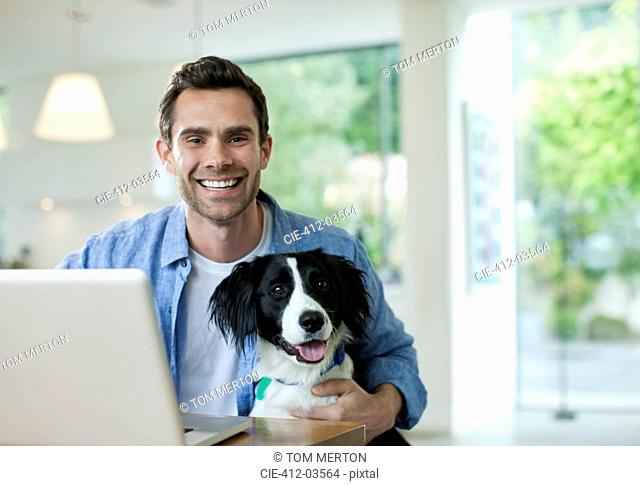 Man with dog using laptop in kitchen