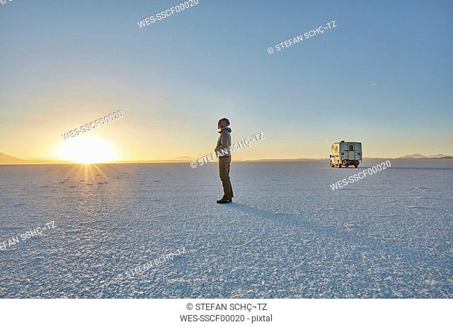 Bolivia, Salar de Uyuni, woman standing at camper on salt lake at sunset