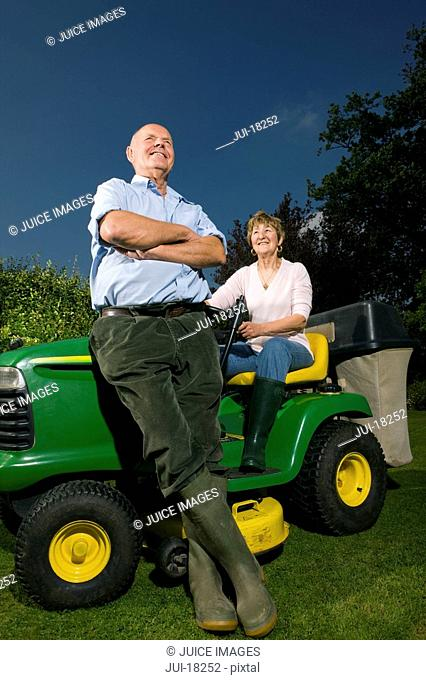 Senior couple and riding lawn mower