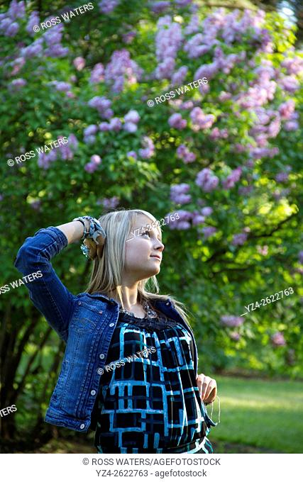 A young woman outdoors in a lilac garden