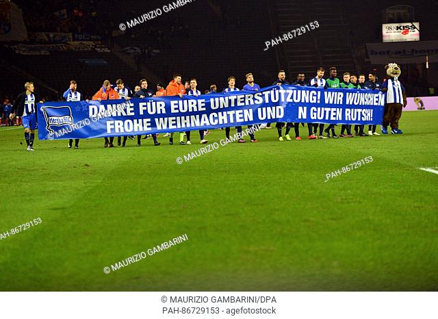 The team of Hertha BSC celebrates its 2-0 win while holding up a banner that reads 'Danke fuer Eure Unterstuetzung! Wir wuenschen frohe Weihnachten und einen...