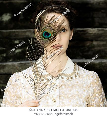 a woman with a victorian dress is holding a peacock feather in front of her eyes
