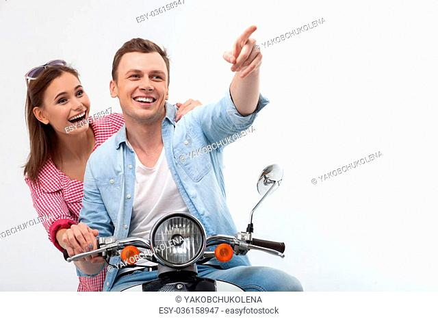 I want to show you something interesting. Beautiful boyfriend and girlfriend sitting on scooter in spring. The man is pointing finger forward and smiling