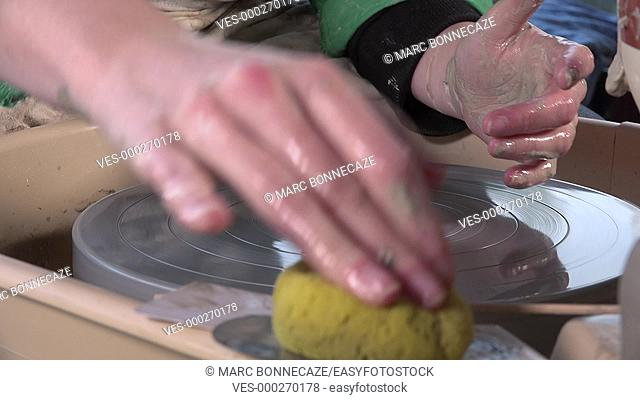 hands shape the rotating block of clay
