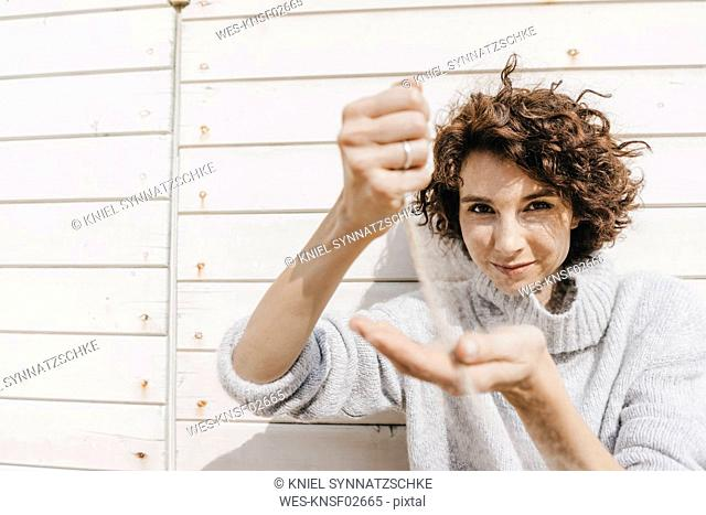 Woman trickling sand through her hands