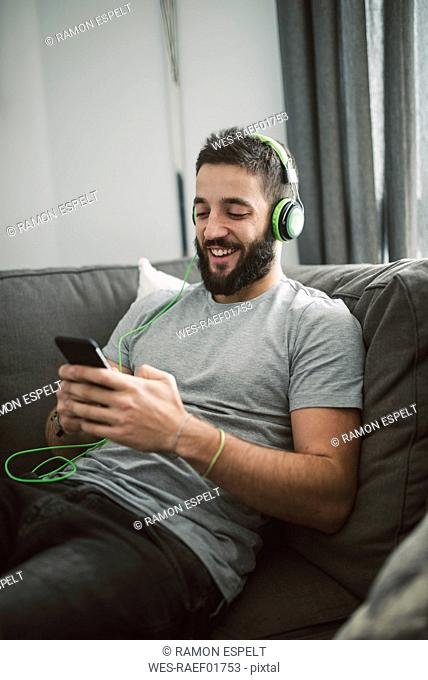 Young man sitting on sofa, listening music from his smart phone