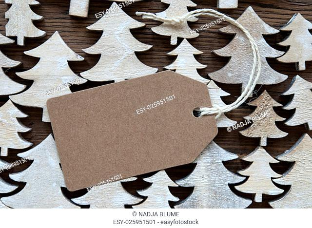 Brown Christmas Label With Ribbon On Wooden Christmas Trees Background. Vintage Style. Label With Copy Space Or Free Text Or Your Text Here For Christmas Or...