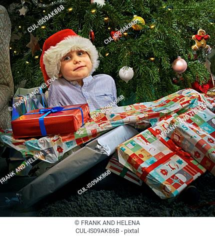 Portrait of cute boy sitting on floor with christmas presents on top of him