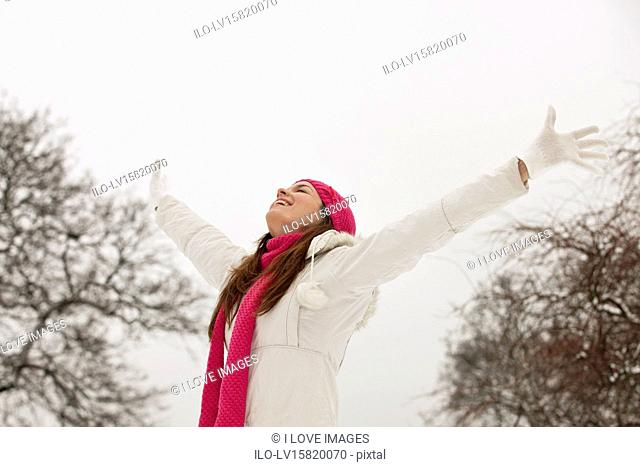 A young woman standing in the snow, arms outstretched