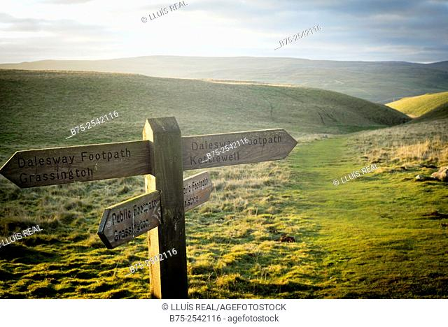 View of a foot path in a green field with a sign post Indications. Dalesway footpath, Grassington, Kettlewell, Public footpath