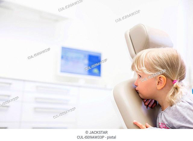 Girl sitting backwards in dentist chair looking away