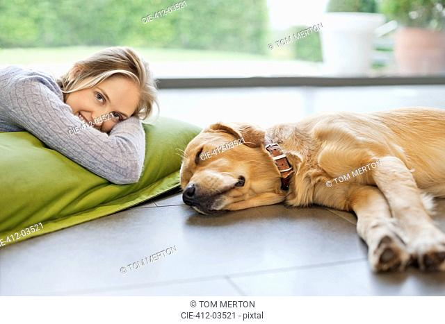 Smiling woman relaxing with dog on floor