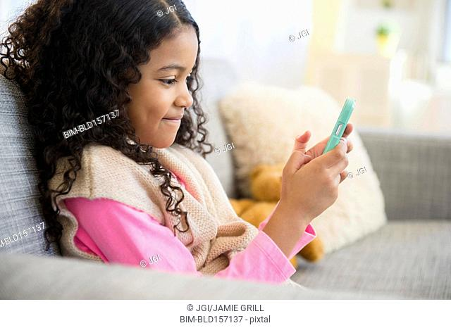 Mixed race girl texting with cell phone on sofa