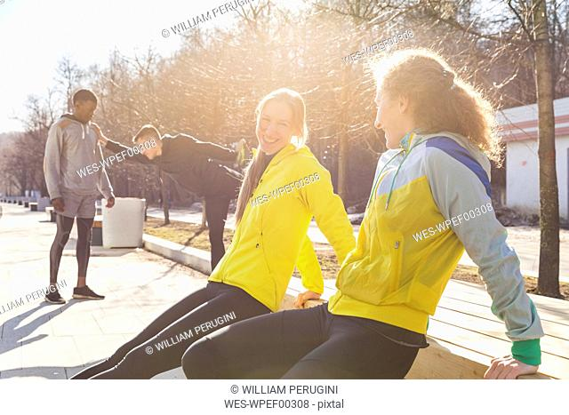 Friends exercising on promenade in the city