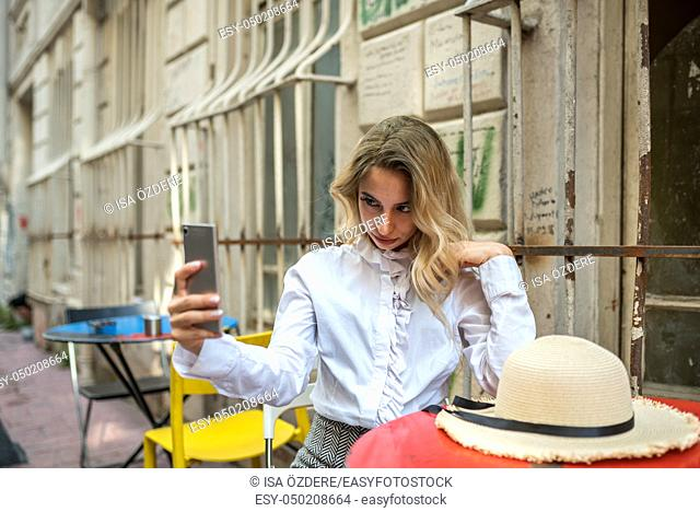 Attractive young beautiful girl uses smart phone while sitting at a cafe outside. Lifestyle concept