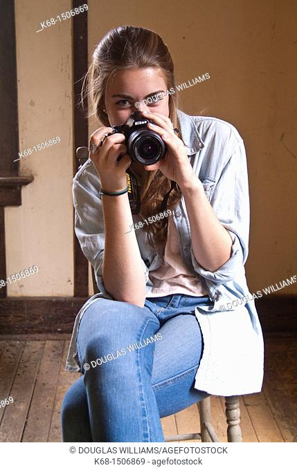 15 year old girl sits in an old abandoned house with her camera
