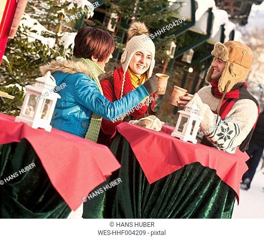 Austria, Salzburg, Man and women at christmas market, smiling