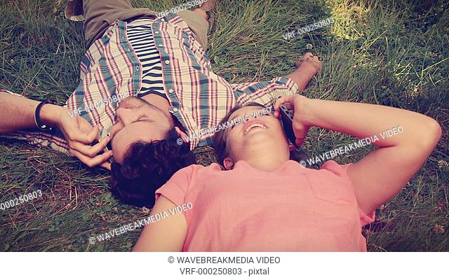 Cute couple lying on the grass and having a phone call on a sunny day