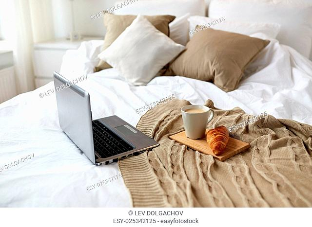 coziness, technology, interior and winter concept - cozy bedroom with laptop computer, coffee cup and croissant on bed at home