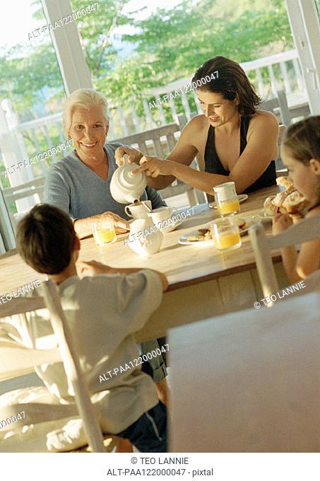 Grandmother, mother and children having breakfast