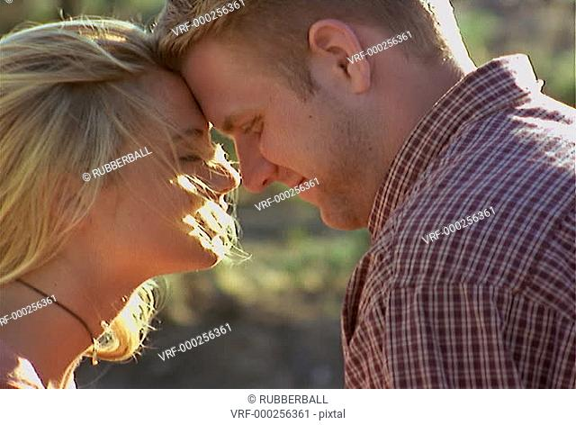 close up of a young caucasian blonde couple who look into each others eyes and sofly kiss each other