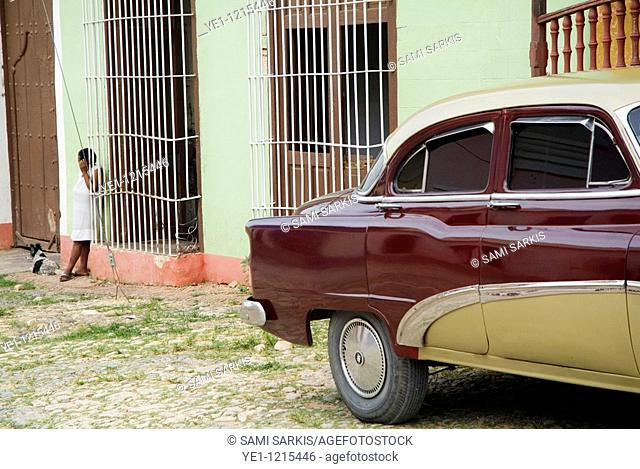 Classic American car and a woman leaning against a wall, Trinidad, Sancti Spiritus, Cuba