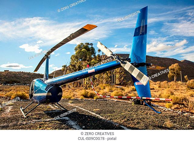 Helicopter on ground in rural landscape, rear view, Cape Town, Western Cape, South Africa