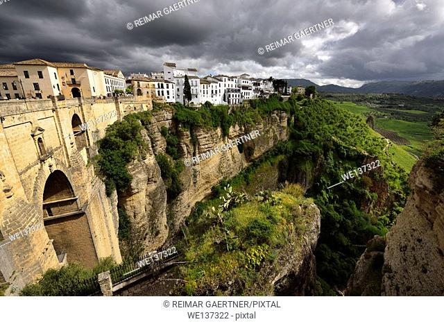 Dark clouds and dappled sunshine on cliff and new bridge of mountain city Ronda Spain