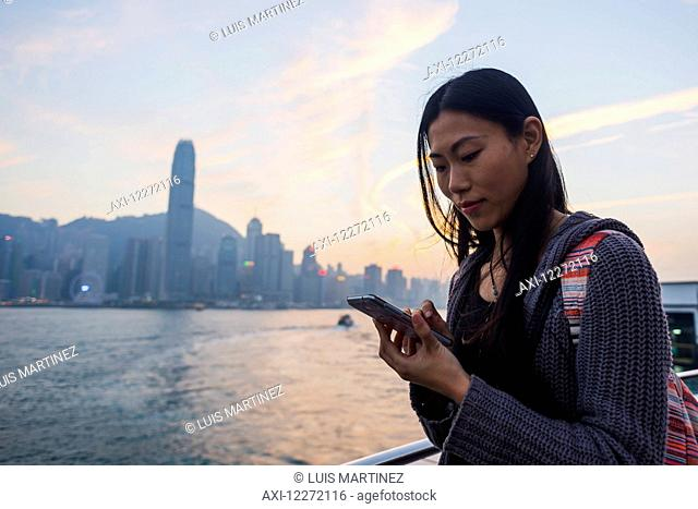 A young woman checks her cell phone at the waterfront with a view of the skyline at sunset, Kowloon; Hong Kong, China