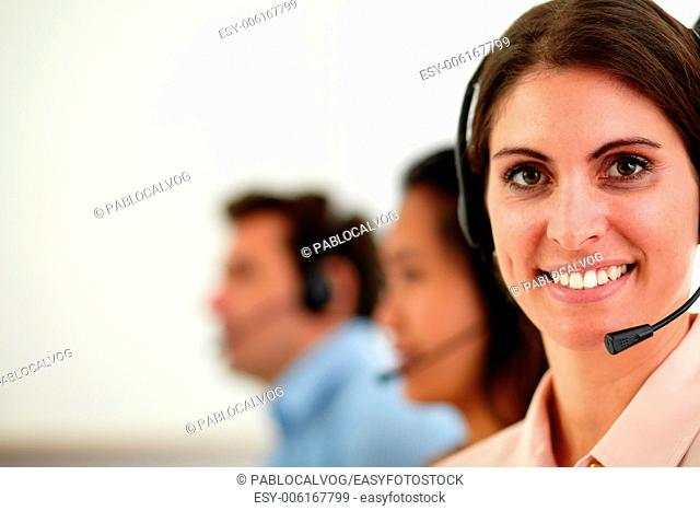 Portrait of caucasian operator woman with earphone smiling at you while sitting on workplace - copyspace