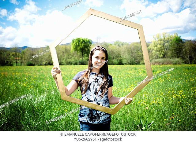 Girl of 10 years with large hexagonal frame, in the middle of a green meadow