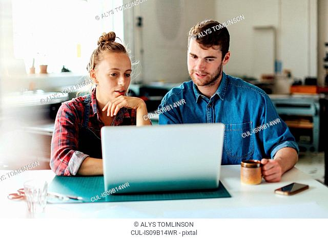 Young craftsman and craftswoman looking at laptop in print studio workshop
