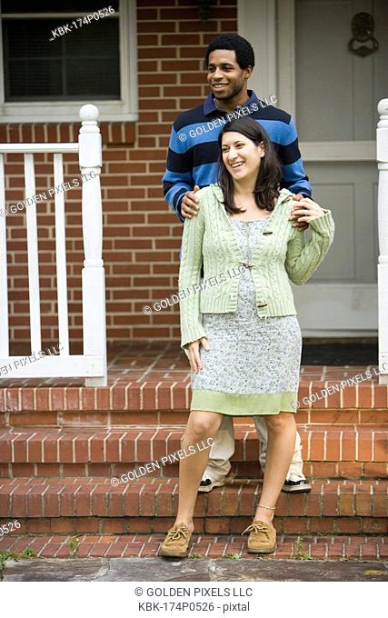 A smiling young inter-racial couple standing on front porch of house
