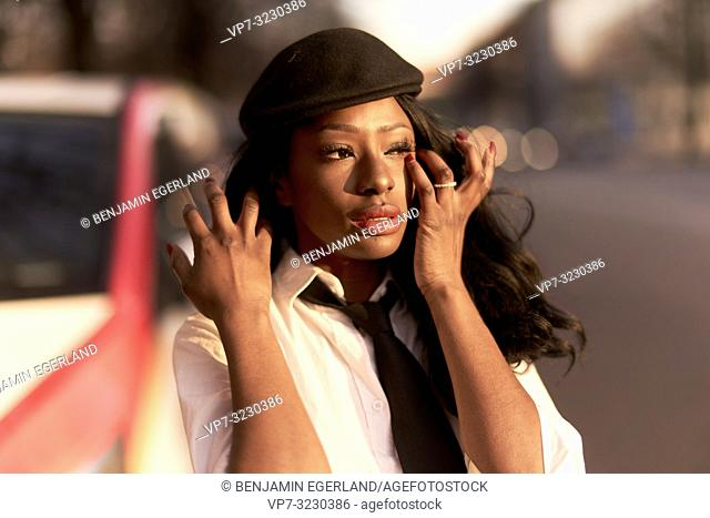 stylish woman touching eye with finger, wearing stylish retro outfit at street in evening sunlight, African Angolan descent, in city Munich, Germany