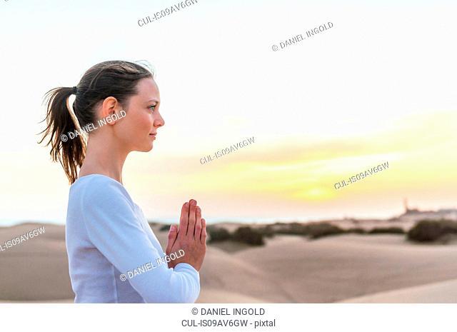 Woman practicing yoga meditation on dunes, Maspalomas, Gran Canaria, Canary Islands, Spain