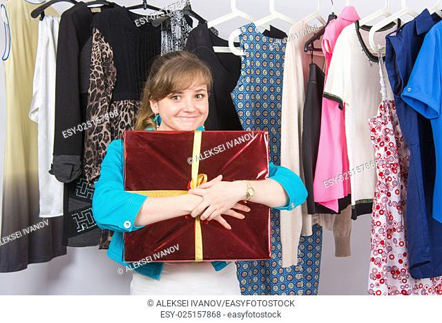 Happy young girl has received a welcome gift in the background hang things on hangers