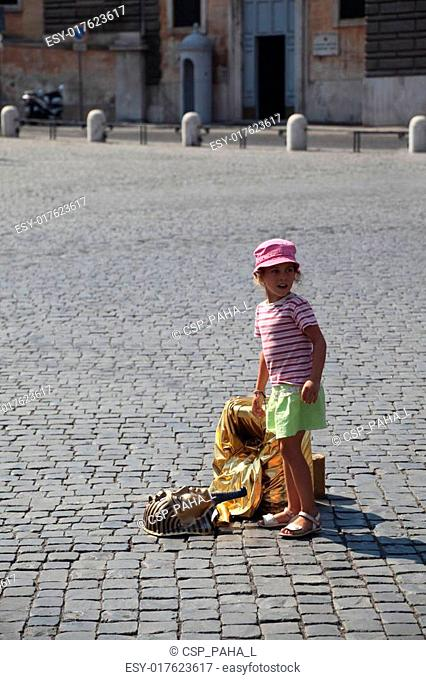 little beautiful girl and fake golden mask of pharaoh on Piazza del Popolo in Rome, Italy