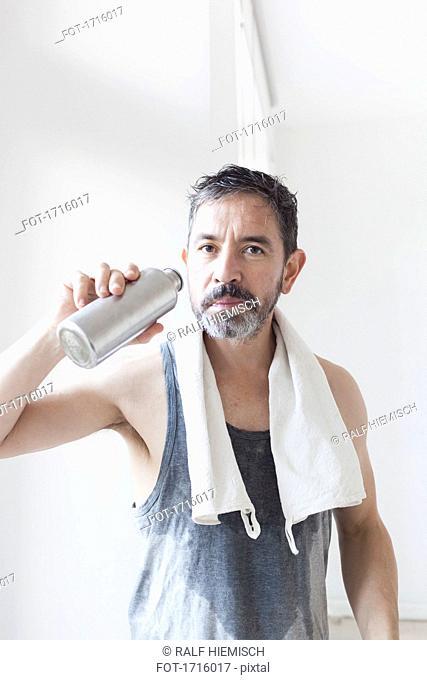 Portrait of mature man holding water bottle
