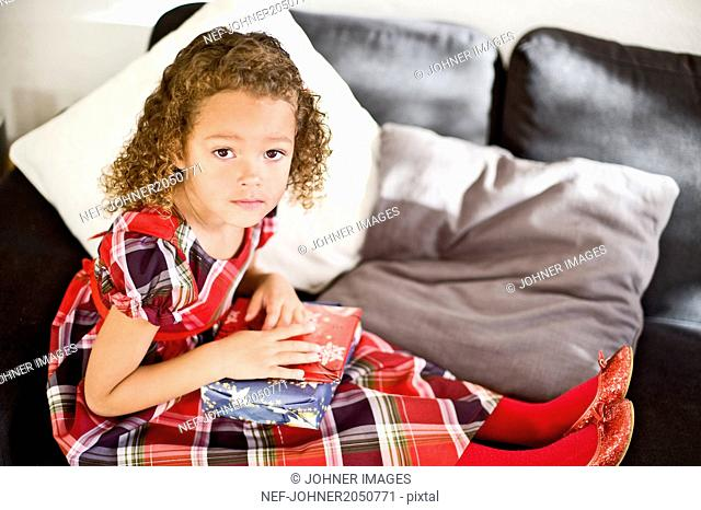Girl sitting on sofa with Christmas gift