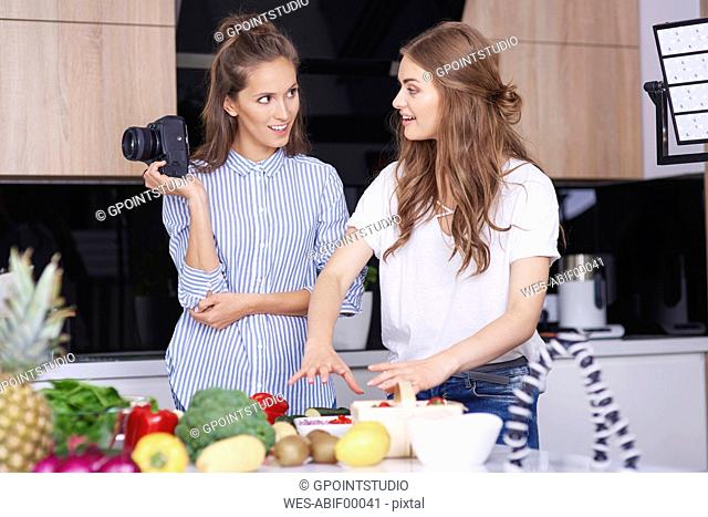 Food bloggers with camera talking in kitchen