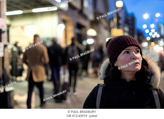 Woman in warm clothing standing on urban sidewalk at night