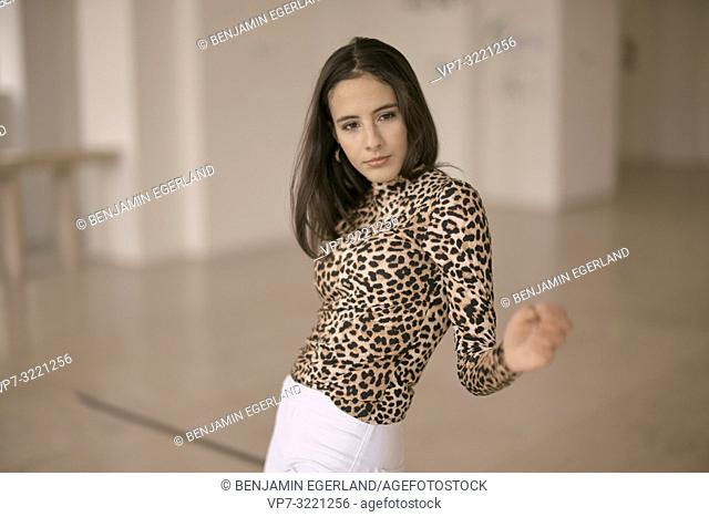 portrait of moving woman dancing indoors, fashionable clothing style, in Munich, Germany
