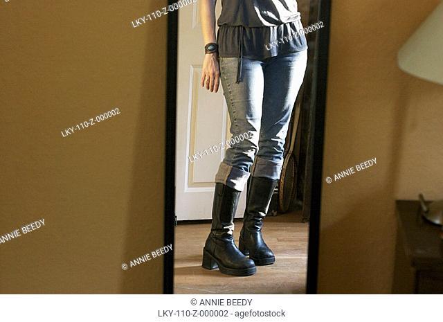 Woman posing in front of mirror, below waist