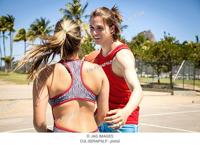 Young couple flirting on basketball court in front of Sugarloaf mountain, Rio De Janeiro, Brazil