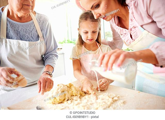 Girl, mother and grandmother easter baking at kitchen counter