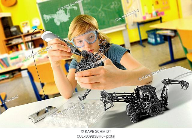 Boy with digital pen and 3D model of excavator in classroom