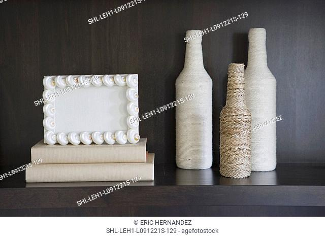 Decorative bottles and frame on bookcase